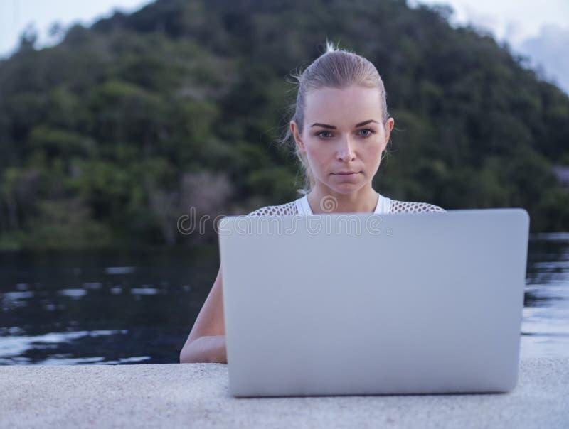 Draußen Porträt von hübschen Blondinen mit Laptop-Computer stockfotografie