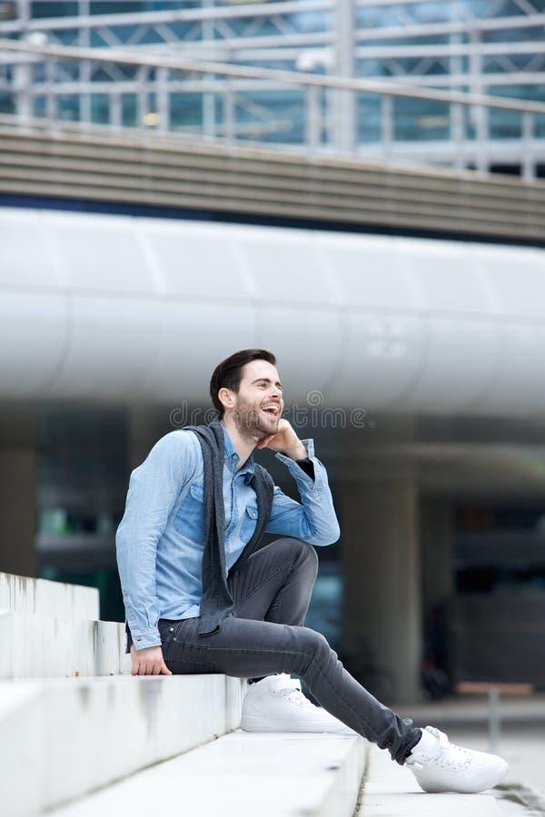 Draußen sitzender und lachender Mann lizenzfreies stockbild