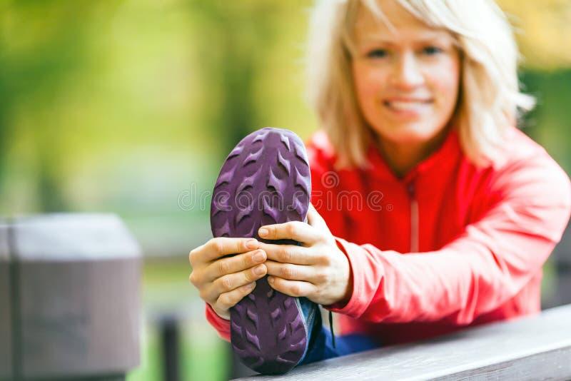 Draußen trainierender und ausdehnender Frauenläufer, Herbstnatur stockfotografie