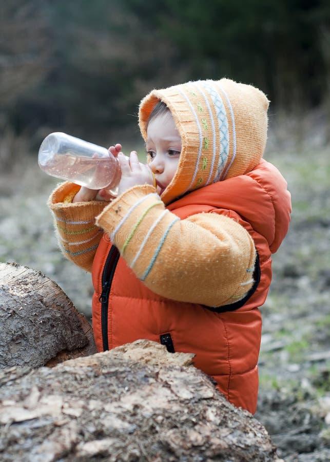 Draußen trinkendes Kind lizenzfreie stockbilder
