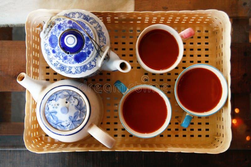 Draufsicht über eine Kunststoffschale mit zwei keramischen weiß-blauen Teekannen und drei Schalen mit thailändischem Tee stockbilder
