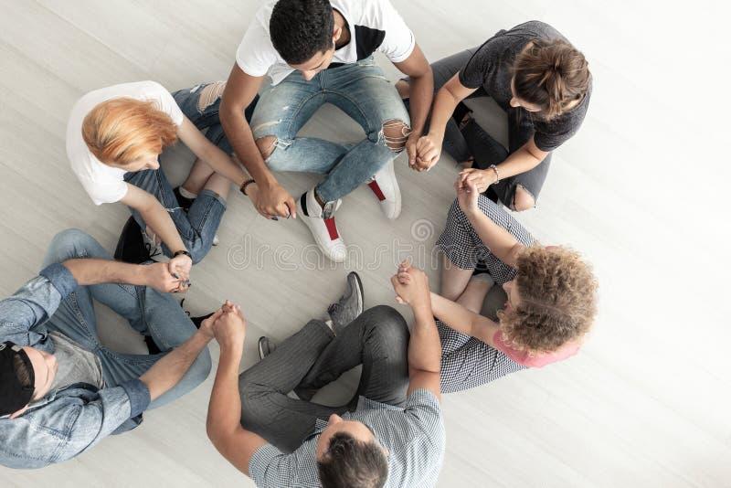 Draufsicht über die Jugendlichen, die in einem Kreis und in einem Händchenhalten duri sitzen stockfotografie