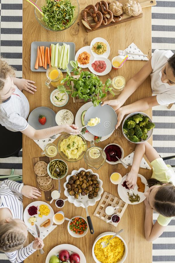 Draufsicht über die Kinder, die gesundes Lebensmittel während Freund ` s birthda essen lizenzfreies stockbild