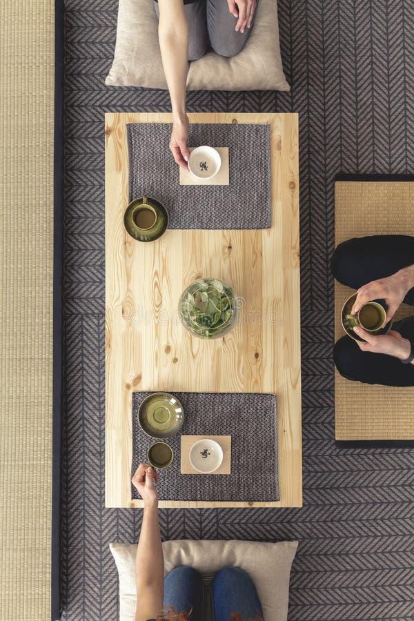 Draufsicht über die Leute, die japanisches Lebensmittel auf Holztisch während m essen lizenzfreies stockfoto