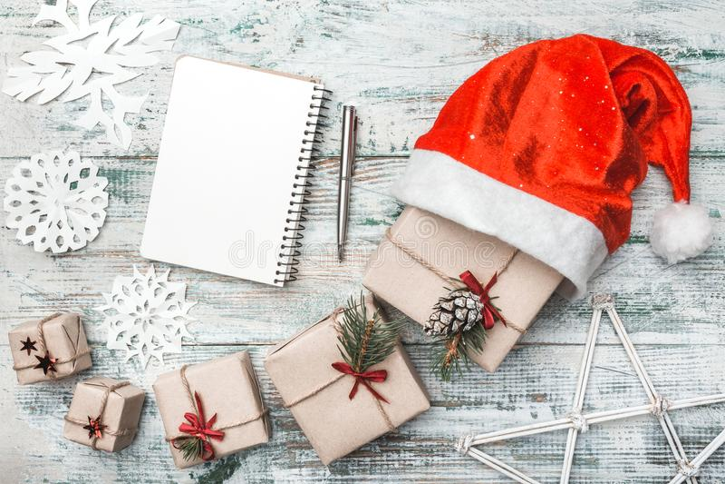 Draufsicht über die netten Weihnachtsgeschenke eingewickelt im weißen Geschenkpapier, Weihnachtsbaumdekorationen in Sankt-` s Hut stockbild