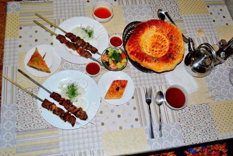 Draufsicht über eine gelegte Tabelle mit Tellern der nationalen orientalischen Küche: Kebab, Flatbread mit indischem Sesam, zwei  stockbild