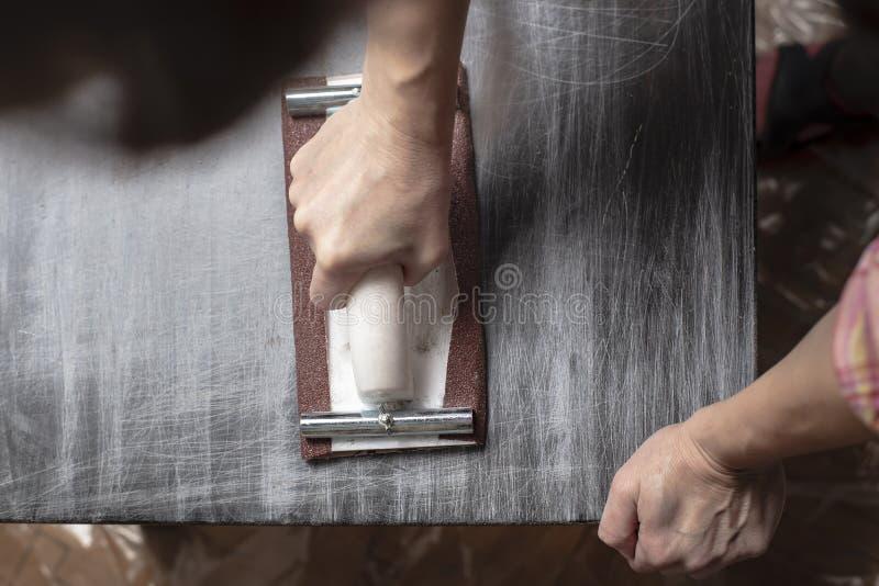 Draufsicht über Frau bereitet die Oberfläche für das Malen und das Versanden durch Hände einer alten hölzernen schwarzen Tabelle  stockbild