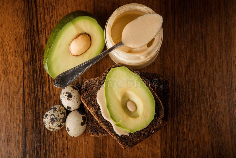 Draufsicht über Glas mit tahini, Roggenbrot, geschnittener Avocado und Wachteleiern lizenzfreies stockbild
