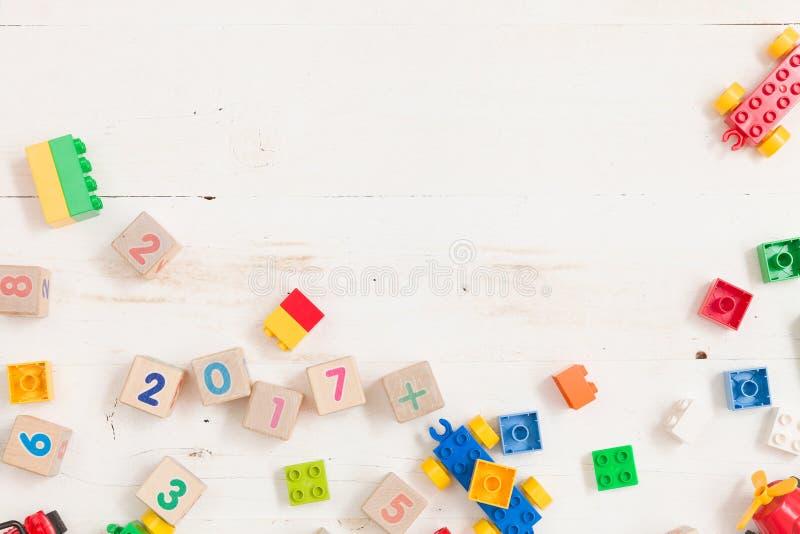 Draufsicht über hölzerne Würfel mit Zahlen und bunte Plastikziegelsteine auf weißem Holztischhintergrund stockfotos