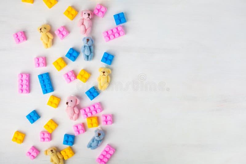 Draufsicht über Mehrfarbenspielzeugziegelsteine und -plüsch betrifft weißen hölzernen Hintergrund lizenzfreie stockfotografie
