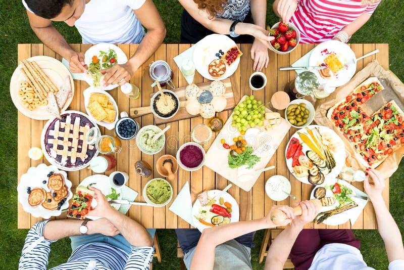 Draufsicht über multikulturelle Gruppe Freunde, die gegrilltes Lebensmittel d essen stockbild