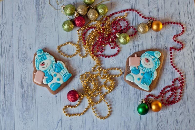 Draufsicht über nette Weihnachten-ginderbreads in Form von den Schneemännern, die nahe Dekorationen auf Holztisch legen lizenzfreies stockfoto