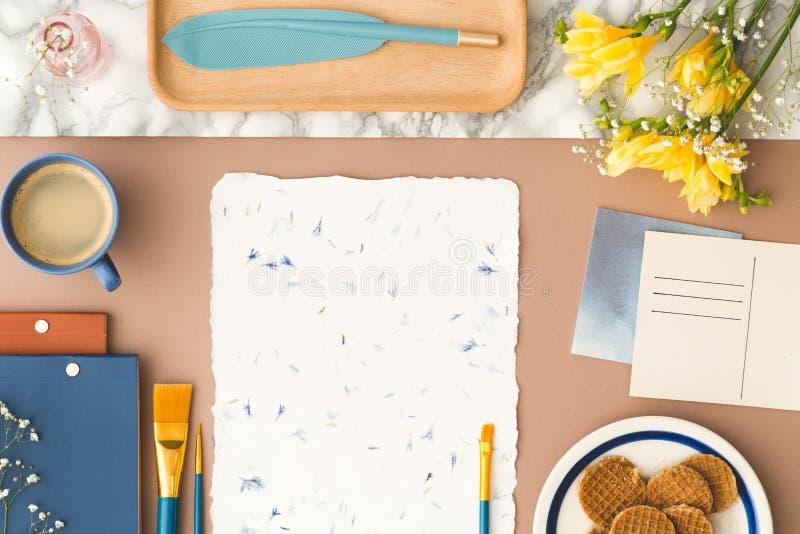 Draufsicht über Schreibtisch mit gelben Blumen, Malereibürste auf dem Papier stockbild