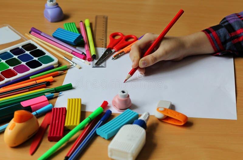 Draufsicht über Tabelle mit leerem Blatt Papier und die Hand des Babys mit Bleistift Zurück zu Schule Farbfarben mit Pinseln, Ble lizenzfreie stockbilder