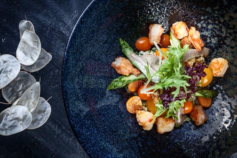 Draufsicht über warme Garnele, Kirschtomate und Spargelsalat diente in der dunklen Platte auf dunklem Hintergrund Flaches Lageleb lizenzfreies stockbild