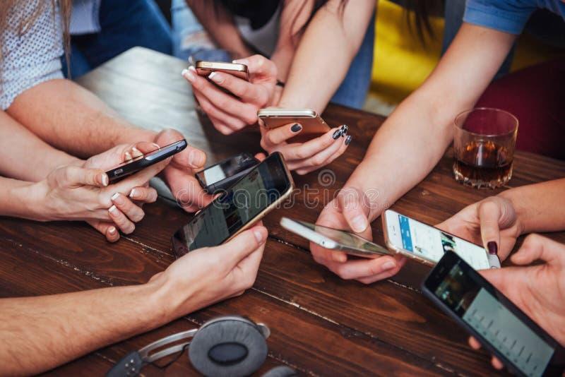Draufsicht übergibt Kreis unter Verwendung des Telefons im Café - gemischtrassiges Freundmobile abhängig Innenszene von oben gena lizenzfreies stockfoto