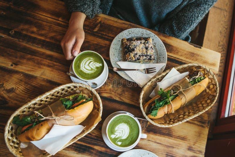Draufsicht - das Mädchen, das im Café sitzt und Becher mit grünem Tee mit Milch nahe bei Stück süßer Torte und zwei hält stockbild