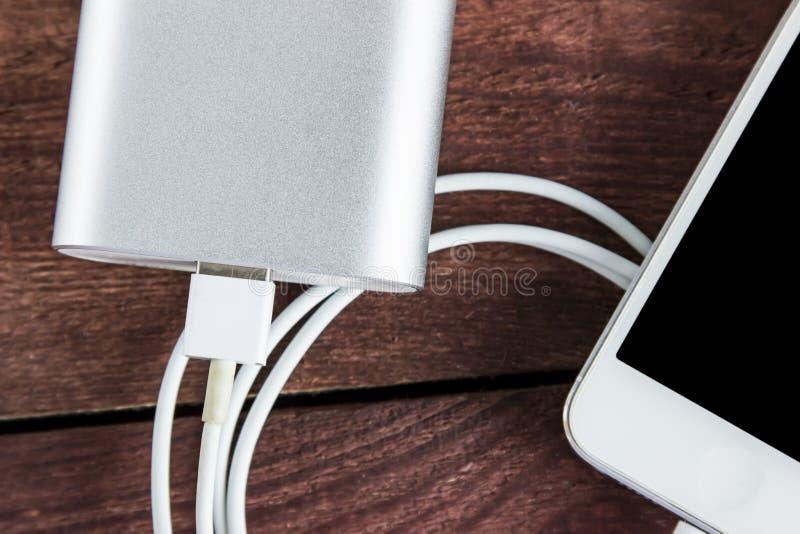 Draufsicht der Aufladung von Smartphone mit grauem powerbank lizenzfreie stockfotografie