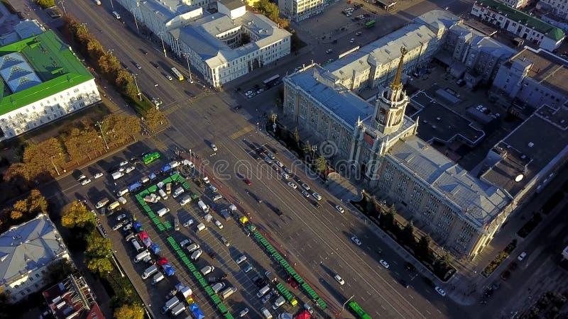 Draufsicht der beschäftigten Stadtstraße Stadtverkehr auf Straße in der Stadt mit Bereich im Sonnenuntergang Quadrat mit Turm und stockfotografie
