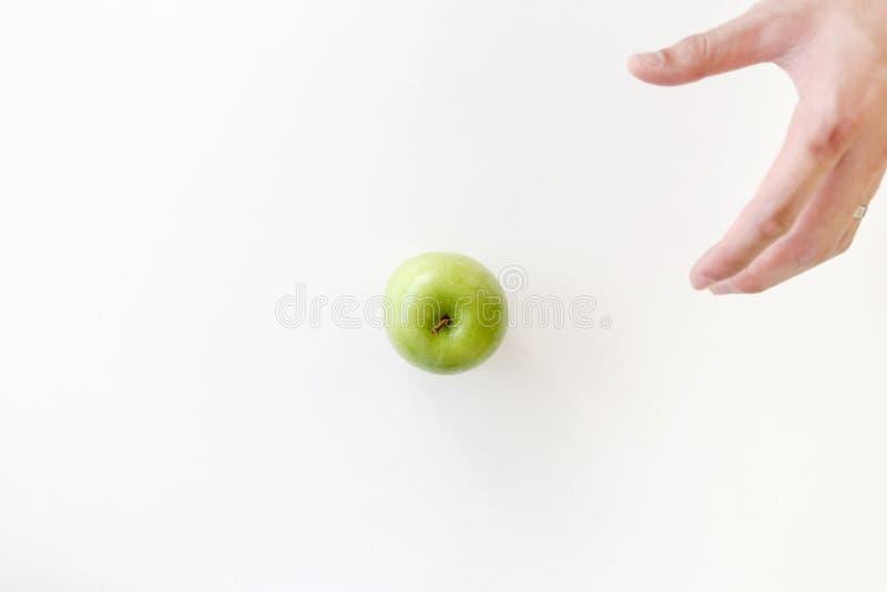 Draufsicht der beweglichen linken Hand für die Ergreifung eines grünen Apfels auf weißem Hintergrund stockfoto