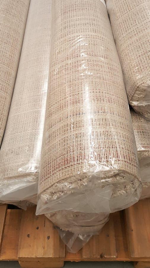 Draufsicht der braunen Geweberolle eingewickelt in der Plastikrollentasche auf hölzernem Palettenvorrat an braunem Gewebe für Mod stockfotos