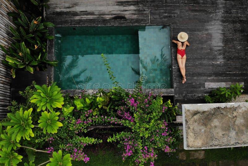 Draufsicht der d?nnen Frau im Bikini und in Hut, die nahe Swimmingpool sich entspannen Raum f?r Text stockfotos