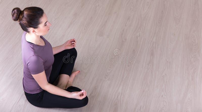 Draufsicht der dünnen Frau sitzend in der Yogahaltung auf dem Boden lizenzfreie stockfotos