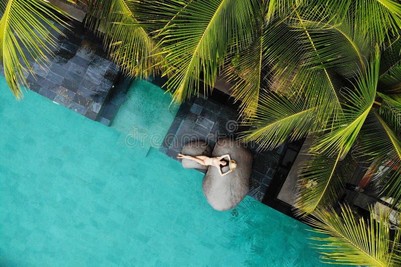 Draufsicht der d?nnen jungen Frau im beige Bikini und im Strohhut, die nahe Luxusswimmingpool und Palmen sich entspannt ferien stockfotos