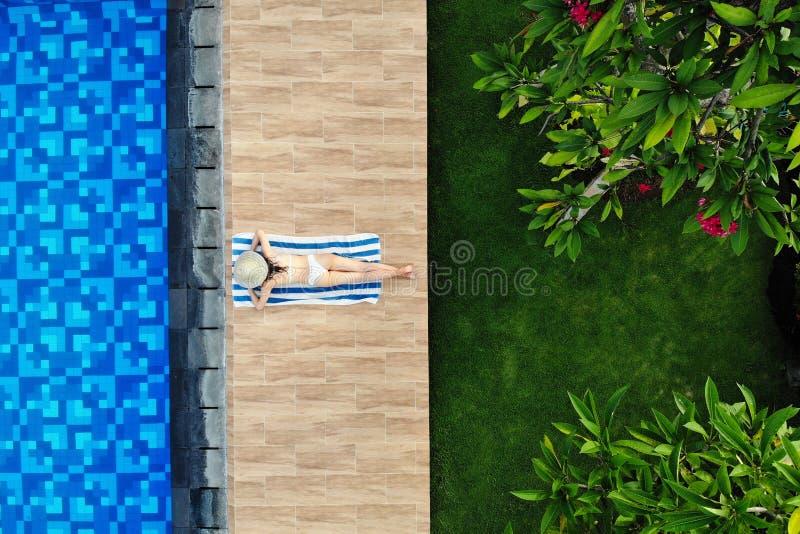 Draufsicht der d?nnen jungen Frau im wei?en Bikini und im Strohhut, die auf Tuch nahe Swimmingpool liegt Hintere Ansicht, ohne Ge lizenzfreie stockbilder