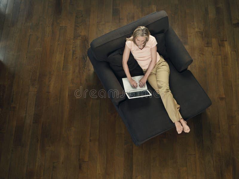 Draufsicht der Frau, die Laptop auf Sofa verwendet lizenzfreie stockfotos