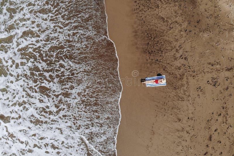 Draufsicht der Frau im roten Bikini und im Strohhut bräunte sich auf Tuch auf Ozeanstrand mit schwarzem Sand Ferien in Bali foto stockbilder