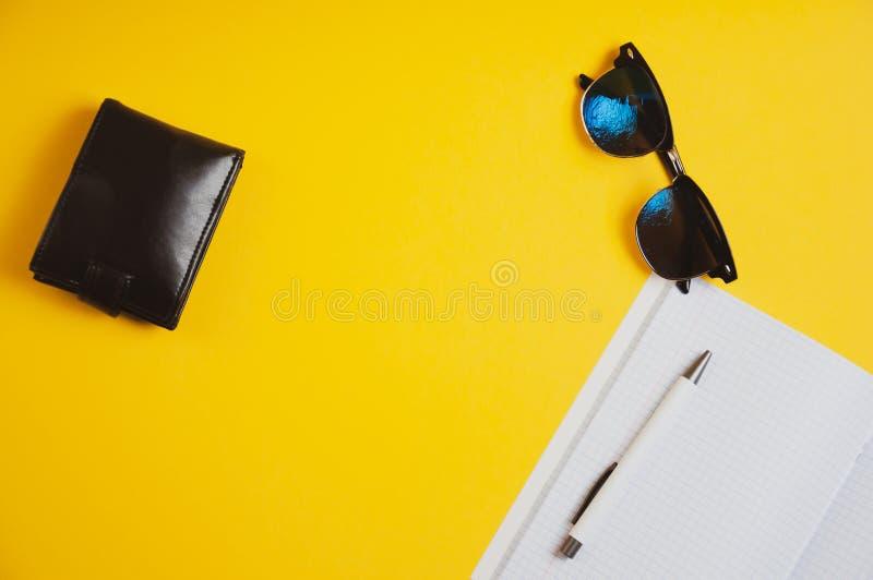Draufsicht der Geldbörse, der Sonnenbrille und des Notizbuches mit Stift auf gelbem Hintergrund stockbild