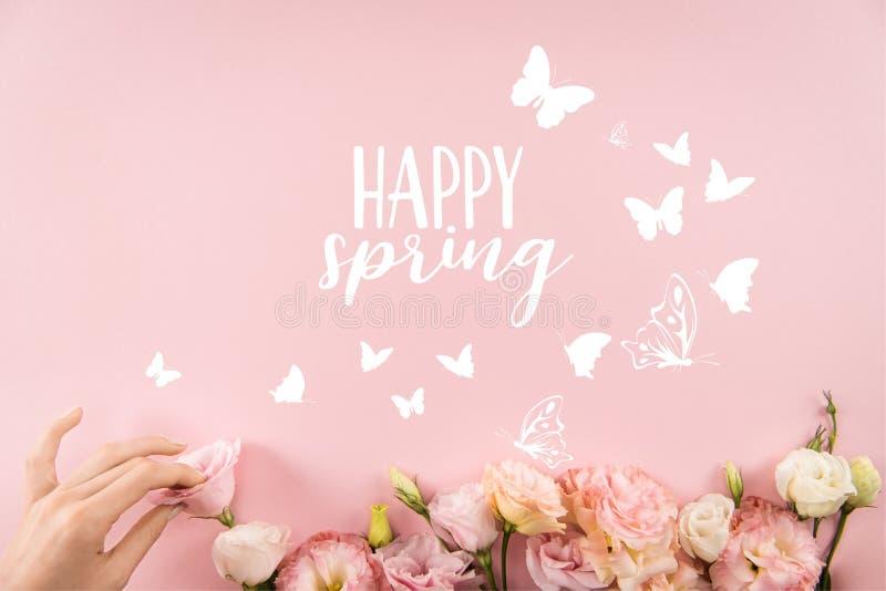 Draufsicht der Hand schöne zarte Blumen mit GLÜCKLICHEM FRÜHLINGS-Zeichen und -schmetterlingen vereinbarend stockfotos
