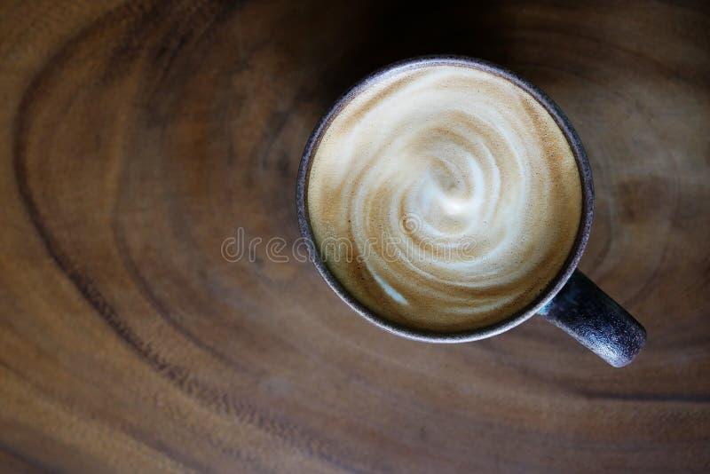 Draufsicht der heißen Kaffeecappuccino Latteschale mit gewundenem Milchschaum auf hölzernem Beschaffenheitstabellenhintergrund stockfotografie