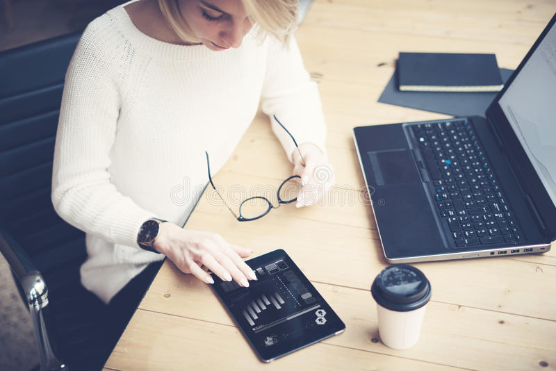 Draufsicht der jungen Schönheit arbeitend am Holztisch mit tragbaren Geräten Weibliche Handrührende digitale Tablette stockfoto