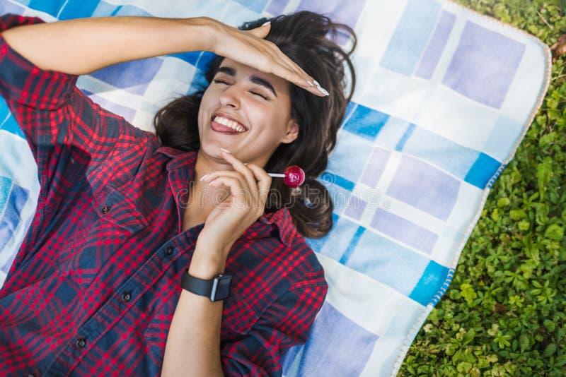 Draufsicht der jungen sexy brunette Frau, die in der Hand mit dem Lutscher trägt das karierte Hemd liegt auf dem Gras im Parkgeni lizenzfreie stockfotografie