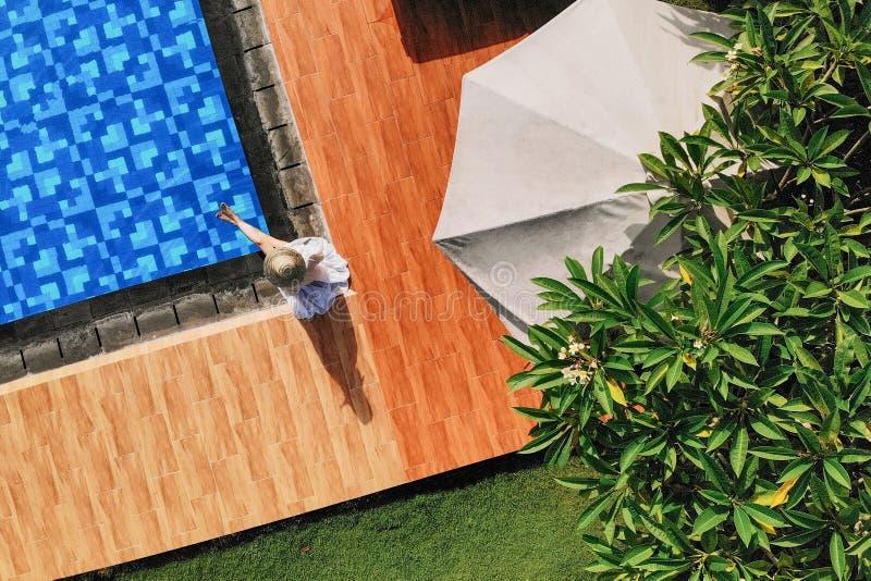 Draufsicht der jungen unerkennbaren Frau im weißen Kleid und im Strohhut, die nahe Swimmingpool sitzt ohne Gesicht drohne lizenzfreies stockfoto