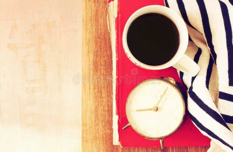 Draufsicht der Kaffeetasse, des alten Uhrbuches und der Decke über Holztisch Gefiltertes Bild lizenzfreie stockfotografie