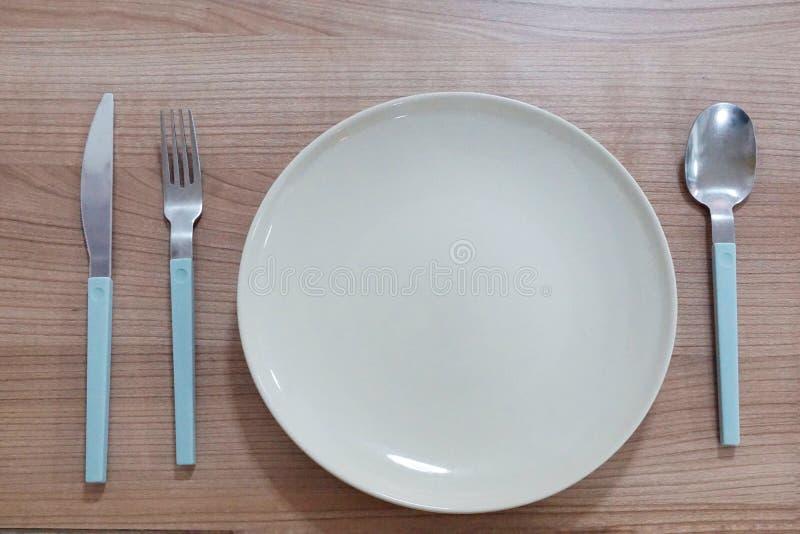 Draufsicht der leeren Platte mit Gabel, Löffel und Messer auf Holztisch lizenzfreie stockfotografie
