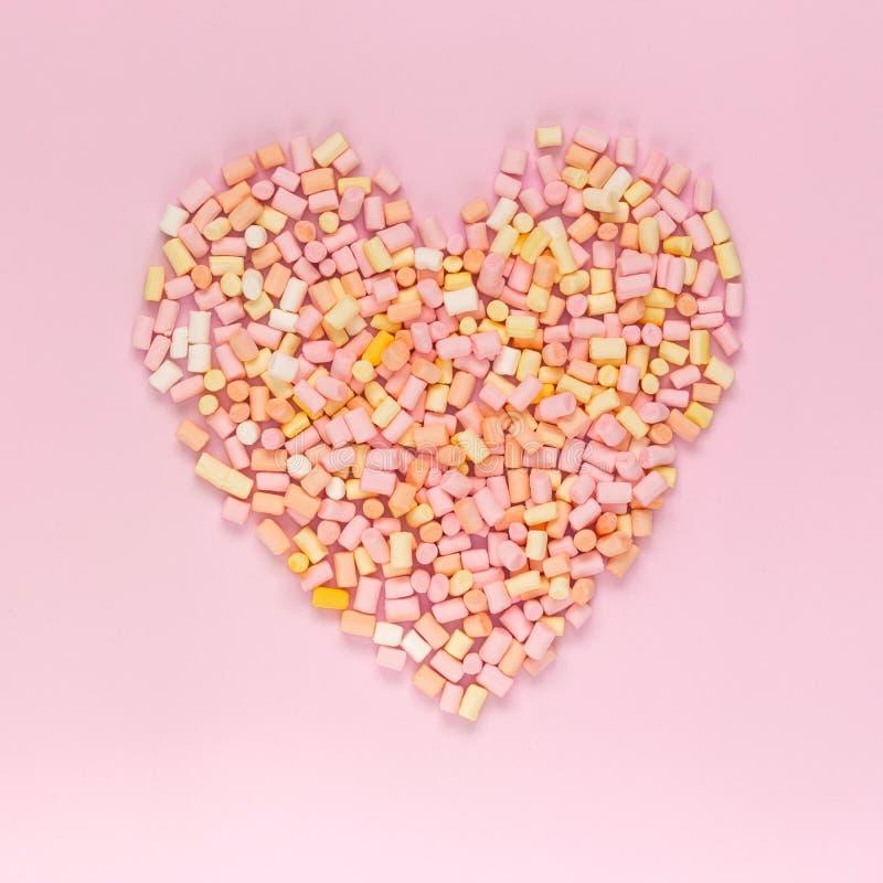 Draufsicht der mehrfarbigen Eibische, die in Form eines Herzens auf einem einfarbigen rosa Hintergrund copyspace, topview liegt, lizenzfreie stockfotos