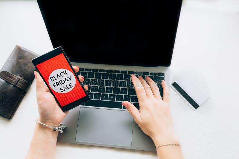 Draufsicht der Nahaufnahme von Händen einer Frau mit schwarzem Freitag bietet am Handy an auf weißem background stockfoto