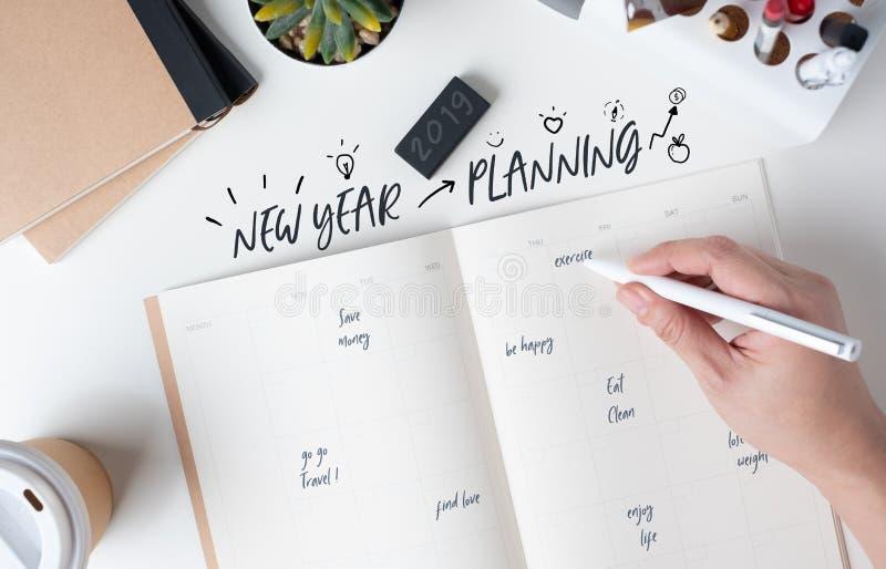 Draufsicht der Planung des neuen Jahres der Handschrift auf offenem Kalenderplaner mit Gekritzelart für Lebenentschließung mit mo lizenzfreie stockfotos
