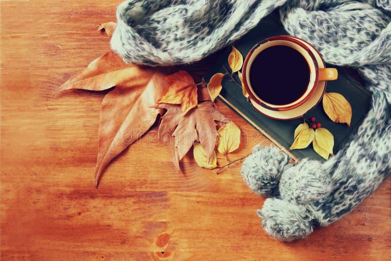 Draufsicht der Schale schwarzen Kaffees mit Herbstlaub, einem warmen Schal und altem Buch auf hölzernem Hintergrund filreted Bild stockbild