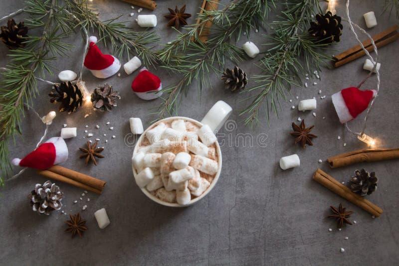 Draufsicht der Schale und der Eibische der heißen Schokolade gegen grauen Hintergrund mit Weihnachtsmotiv stockbilder