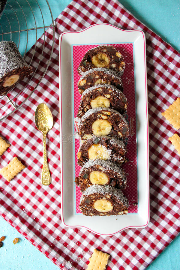 Draufsicht der Schokoladensalamirolle mit Bananen- und Kokosnussscheiben stockbilder