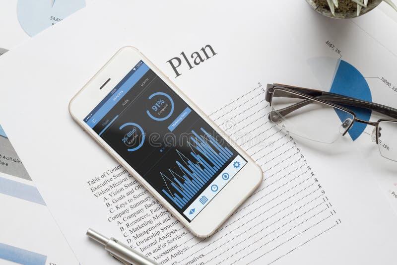 Draufsicht der Schreibtischtabelle mit Diagrammdiagramm auf scheinbarem hohem Smartphone auf weißer Schreibtischtabelle Geschäfts lizenzfreie stockfotografie