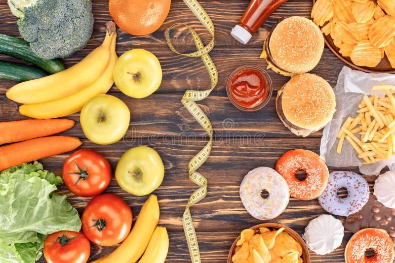 Draufsicht der sortierten ungesunder Fertigkost, der frischen Früchte mit Gemüse und des messenden Bands auf hölzernem lizenzfreie abbildung