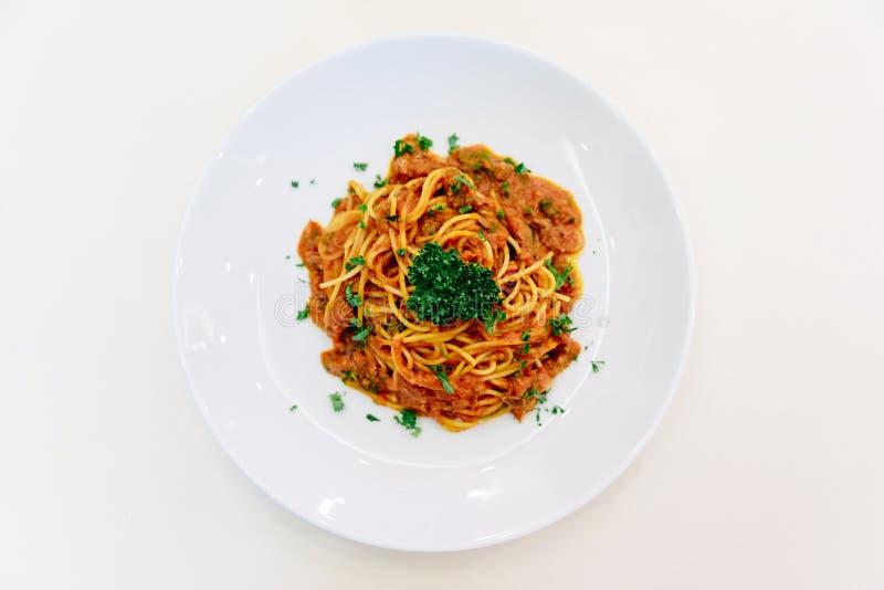Draufsicht der Spaghetti-Soße mit Rinderhackfleisch in der weißen Schüssel auf weißer Tischdecke mit silbernem Löffel lizenzfreies stockbild