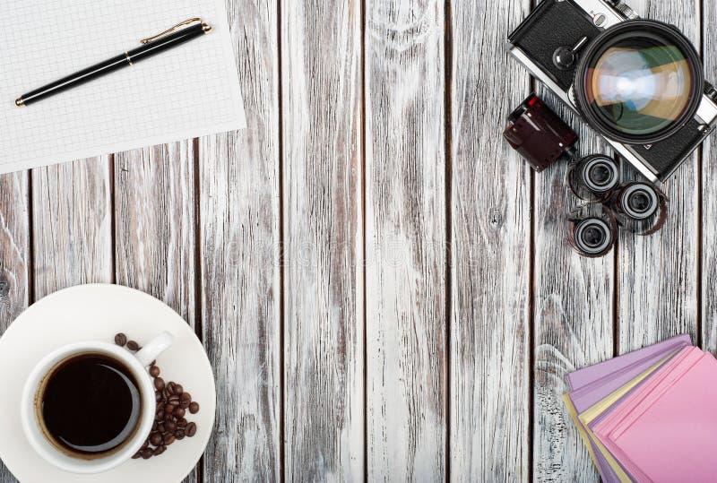 Draufsicht der Weinlesefilmkamera, Aufkleber, Kaffeetasse auf einem woode stockfotografie