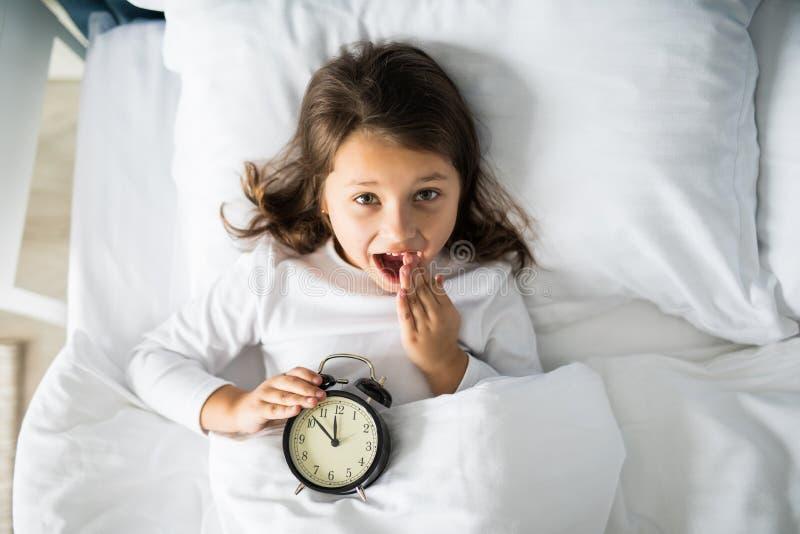 Draufsicht des überraschten Mädchens, das ihren Mund mit der Hand, zu Hause liegend im Bett mit Wecker bedeckt und betrachten Kam stockfotografie